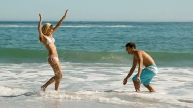 Delighted couple playing on the beach — Stockvideo