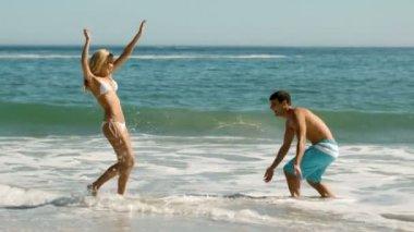Glad par spelar på stranden — Stockvideo