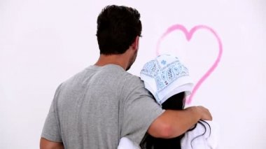 Couple heureux en regardant un coeur peint rose — Vidéo