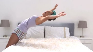 Cute woman falling on her bed full of pillow feathers — Stock Video