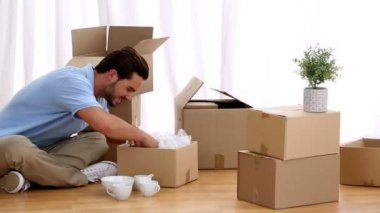 Attractive man opening his moving boxes — Stock Video