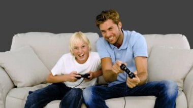 Father and son playing video games on the sofa on grey background — Stock Video