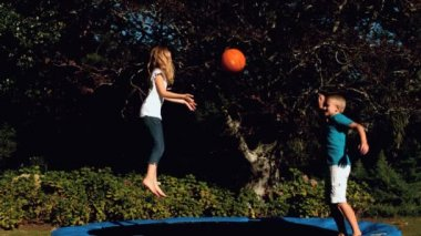 Cheerful siblings having fun with a basketball on a trampoline — Stock Video