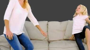 Mother and daughter jumping on the sofa on grey background — Stock Video