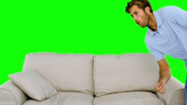 Man jumping on the sofa on green screen — Stock Video