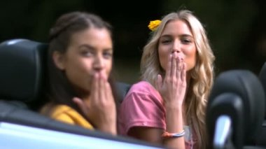 Girls sending kisses while friend laughs in car — Stock Video