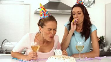 Woman blowing candle while celebrating her birthday with a friend — Stock Video