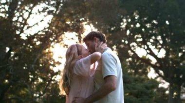 Encantado de pareja besándose frente a la puesta del sol — Vídeo de Stock