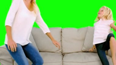 Mother and daughter jumping on the sofa on green screen — Stock Video