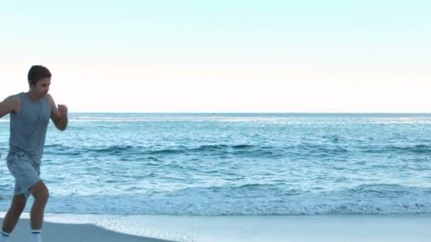 Atractiva pareja corriendo en la playa — Vídeo de stock
