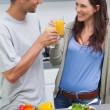 Lovely couple clinking glass of orange juice — Stock Photo