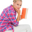 Attractive young woman holding a book and sitting on a stack of — Stock Photo #28046549
