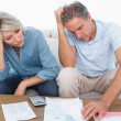 Stock Photo: Anxious couple going over bills