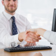 Smiling businessman shaking hands with a co worker — Stock Photo