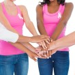 Women wearing breast cancer ribbons putting hands together — Stockfoto #28047125