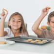Siblings raising homemade cookies — Stock Photo