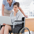 Disabled businesswoman looking at laptop with her colleague — Stock Photo