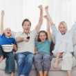 Family watching television and raising arms — Stock Photo #28047387