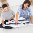 Woman and her husband looking at their house plans — Stock Photo #28047501