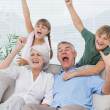 Stock Photo: Grandparents and grandchildren raising arms