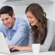 Happy couple using a laptop in the kitchen — Stockfoto