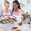 Cheerful woman showing freshly baked cookies to friend — Stock Photo