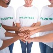Group of female volunteers with hands together — Stock Photo