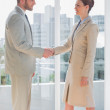 Business people shaking hands and smiling — Stock Photo