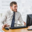 Frustrated businessman looking at his computer — Stock Photo