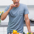 Attractive man eating a slice of bell pepper — Stock Photo
