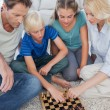 Portrait of a cute family playing chess — Stock Photo