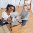 Happy housemates unpacking boxes in new home — Stock Photo