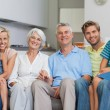 Extended family sitting on couch in living room — Stock Photo #28049473