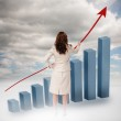 Businesswoman drawing a red arrow over a growing chart — Stock Photo #28049491