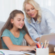 Stock Photo: Mother helping her daughter to do homework
