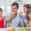 Foto de Stock  : Happy family eating pizzslices