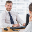 Stock Photo: Businessmsitting with co worker at his desk
