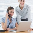 Businesswoman calling and smiling at camera with co worker — Stock Photo