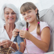 Young girl and her granddaughter knitting together — Stock Photo