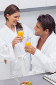 Couple clinking their glass of orange juice — Stock Photo