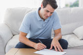 Handsome man writing on a paper — Stock Photo