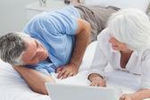 Пара лежа в постели и используя ноутбук — Стоковое фото
