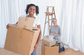 Young friends unpacking in their new home and smiling at camera — Stock Photo