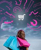 Donna tenendo le borse della spesa e guardando un disegno — Foto Stock