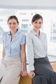 Businesswomen leaning on desk — Stock Photo