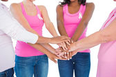 Women wearing breast cancer ribbons putting hands together — Stock Photo