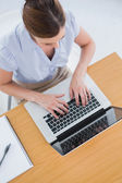Businesswoman typing on her laptop overhead — Stock Photo