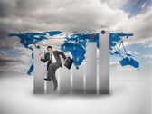 Businessman jumping in front of a chart and a world map — Stock Photo
