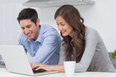 Happy couple using a laptop in the kitchen — Stock Photo