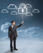 Businessman holding a floating padlock around clouds — Stock Photo